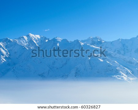 Snow covered mountains rise above morning mist on sunny day - stock photo