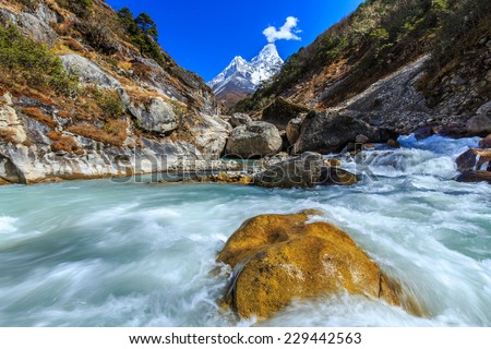 Snow covered mountains, rocky peaks and glacier stream in Himalaya - stock photo