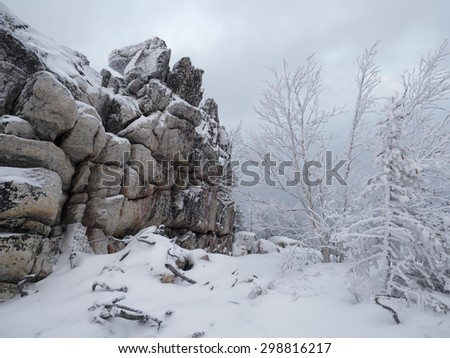 Snow covered rocks and trees on top of the Yalangas mountain in cloudy day, late autumn, South Urals, Russia - stock photo
