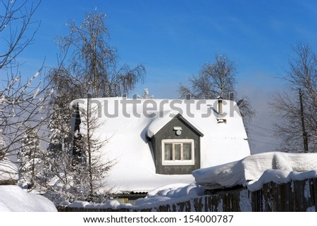 snow-covered roof of a village house on the background of bright blue sky - stock photo