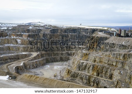 Snow covered stone quarry in the winter with all the tools and buildings ready to work - stock photo
