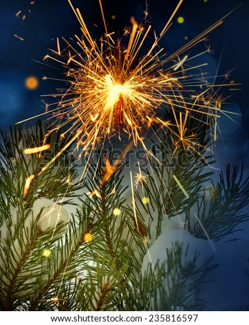 snow covered tree and sparkler - stock photo