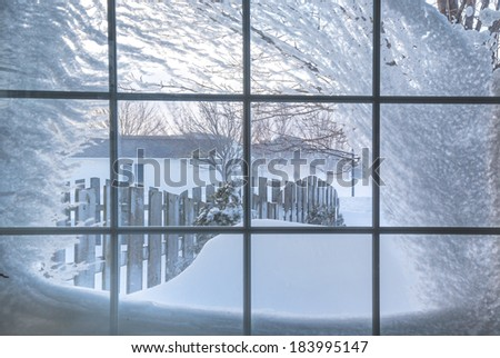 Snow covered window with a view out into a residential neighborhood. - stock photo