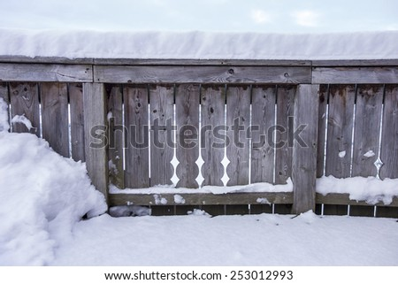 Snow covered wooden fence - stock photo