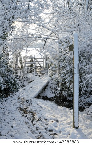 Snow covered woodland footpath leading to timber kissing gate giving access to public footpath across farmland - stock photo