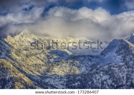 Snow covers the Wasatch mountains in January 2014 with clouds hanging over them low. shot taken from the Salt Lake City Valley in Utah USA / Winter on the Wasatch  - stock photo