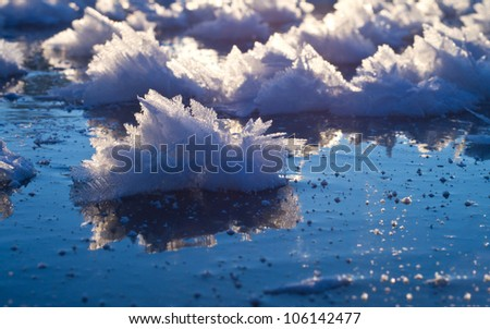 Snow crystal with reflection on blue ice. - stock photo