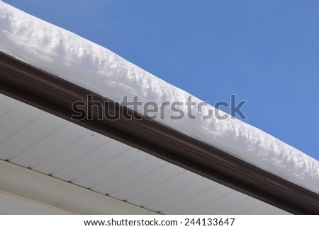Snow deposit on the roof - stock photo
