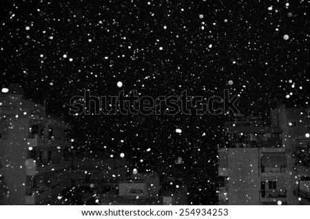 Snow falling over city buildings at night. Black and white. - stock photo