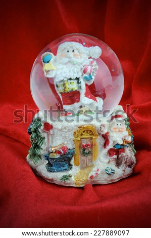 Snow Globe in the Santa on the red velvet - stock photo