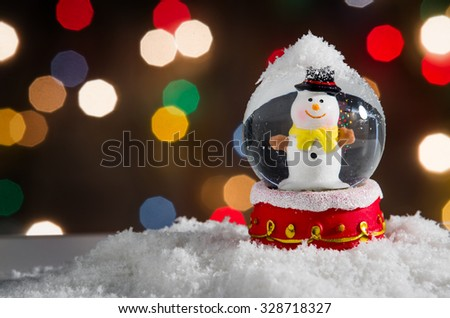 Snow globe with snowman over christmas lights background - stock photo