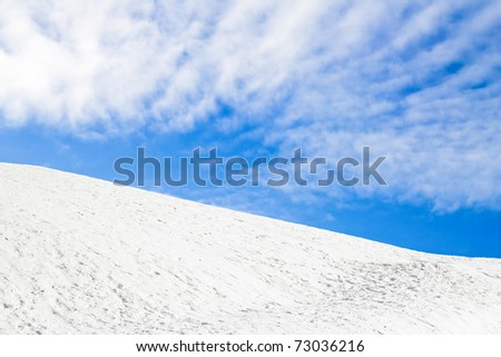Snow Hill and blue sky with clouds - stock photo