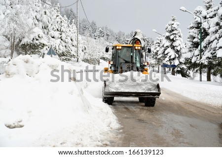 snow loader  cleaning road from ice - winter transportation background - stock photo