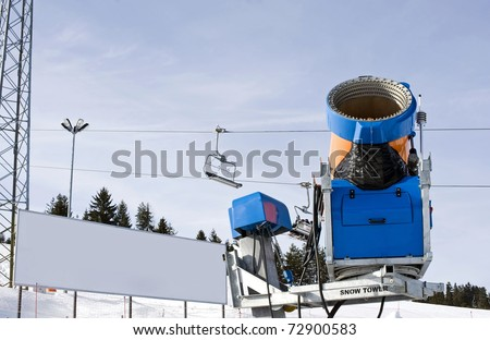 Snow making machine with blank billboard in the background, you can place your own text. - stock photo