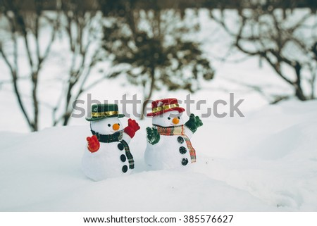 Snow man stand among pile of snow in park. Sunshine is warming but cold at Hokkaido, Japan. - stock photo