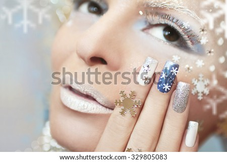 Snow manicure with silver nail Polish and snowflakes. - stock photo