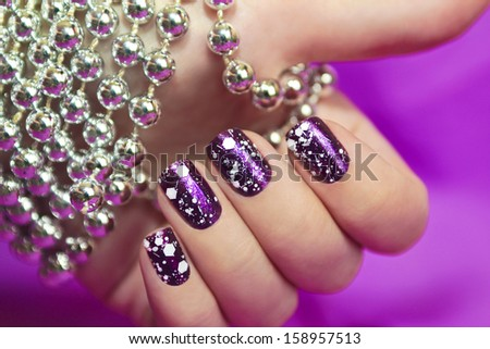 Snow manicure with the design of the white crumbs on violet brilliant varnish for the nails. - stock photo