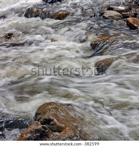 Snow melt runoff gurgling over Rocks in it's path - stock photo