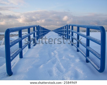 snow on a Lake Michigan pier with blue railings - stock photo