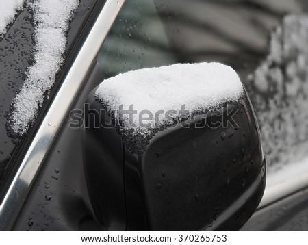 Snow on car's rear view mirror - stock photo