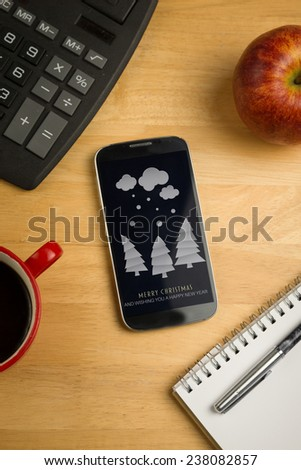 Snow on fir trees against overhead of smartphone with calculator - stock photo