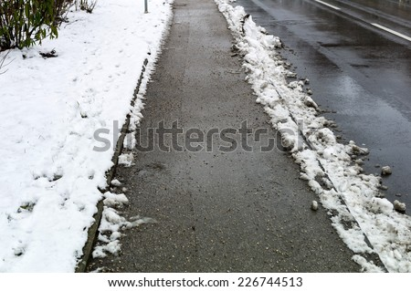 snow on sidewalk and street, symbol for accident risk and photo r���¤umpflicht - stock photo