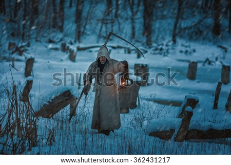 Snow on the field is the man with the scythe of death. He is dressed in a hoodie and causes horror. - stock photo