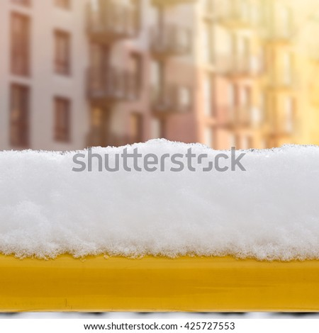snow on the yellow bench in the yard, apartments background - stock photo