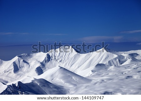 Snow plateau and blue sky. Caucasus Mountains, Georgia, view from ski resort Gudauri. - stock photo