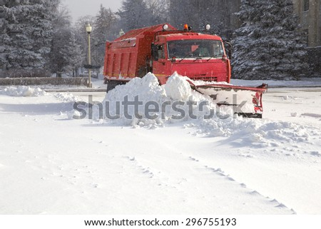 Snow plow cleaning snow from city road - stock photo