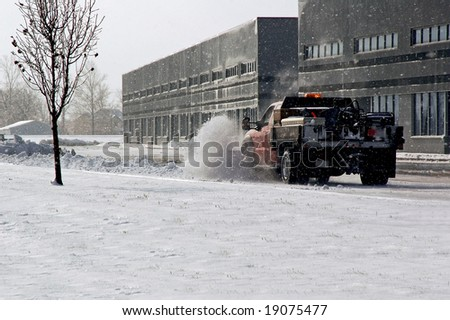 Snow plow cleaning up the parking lot. - stock photo