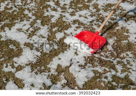 Snow removal. Red plastic Shovel in snow, ready for snow removal, outdoors.  - stock photo