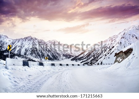 Snow road in the mountains near Big Almaty Lake at sunrise in Kazakhstan - stock photo