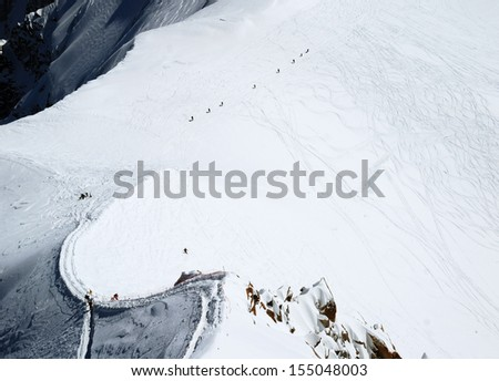 Snow slope with range of mountain-skiers trained by guide, steep peak and path in the foreground, dark declivity behind - stock photo