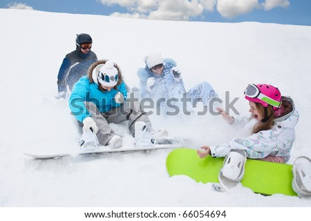 Snow splashes and three young girls sit on the bottom of the mountain - stock photo