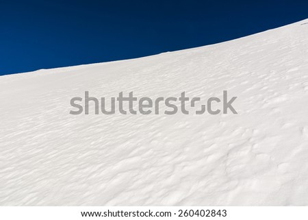 Snow steep slope in the mountains  - stock photo