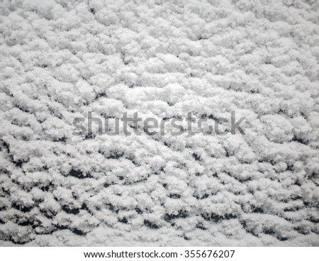 Snow texture in winter season. Fluffy flakes of snow on the surface of the glass. - stock photo