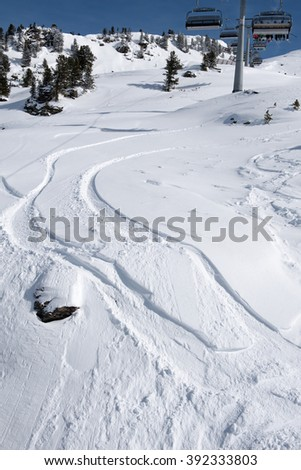 Snow tracks bending in a curve under the ski lift in the Zillertal Arena, Austria - stock photo