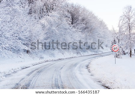 Snow tracks on a country road and 60 mph/km signs. - stock photo