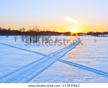Snow ways. Trace of snowmobile crossing a ski track against sunset - stock photo