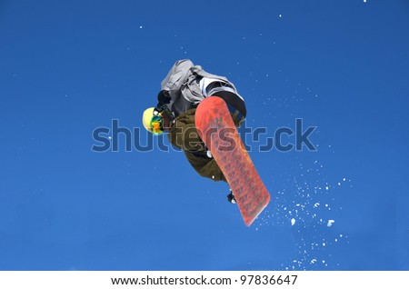 Snowboard free rider making a high jump overhead and spraying snow in his wake in a blue sky. - stock photo