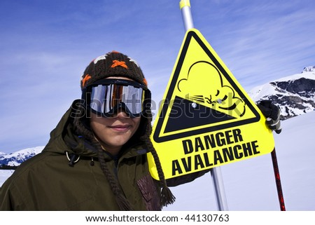 Snowboarder and Danger sign in ski station, Alps, Areches - stock photo
