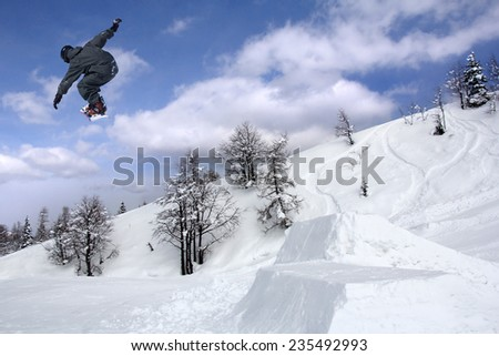 Snowboarder at extreme jump in high mountains at sunny day - stock photo