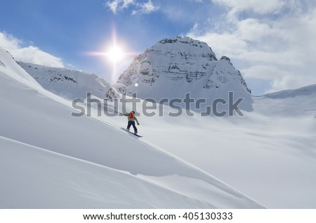 Snowboarder coming down a steep slope in sunny mountains - stock photo