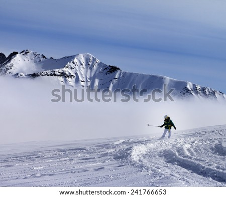 Snowboarder downhill on off-piste slope with newly fallen snow. Ski resort Gudauri. Caucasus Mountains, Georgia. - stock photo