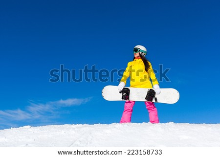 snowboarder girl standing hold snowboard, snow mountain slope copy space blue sky - stock photo