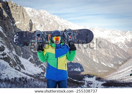 Snowboarder hold snowboard on top of hill close up portrait, snow mountains snowboarding on slopes - stock photo