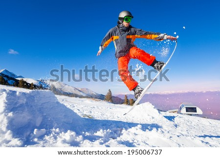 Snowboarder holding board during jump - stock photo