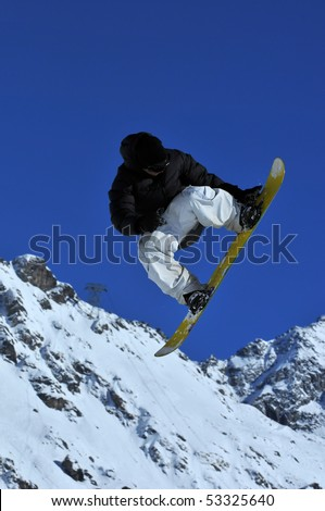 snowboarder in black and white performing a high jump - stock photo