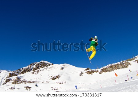 Snowboarder in colorful clothing performing a bold move in snow park. Trademarks have been removed. - stock photo